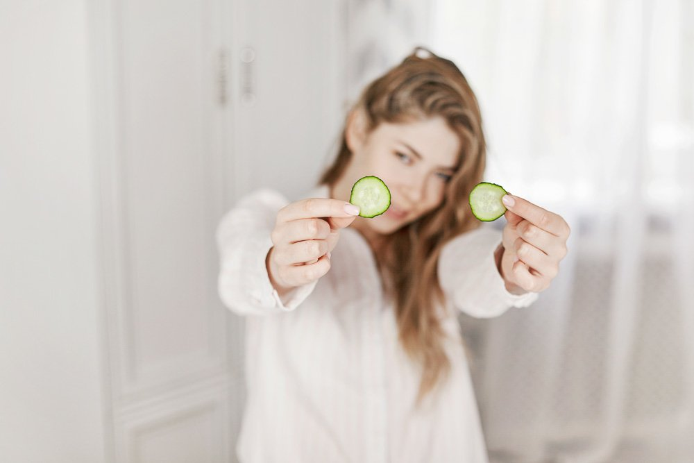 A charming young girl makes a face mask from a cucumber. example image 1