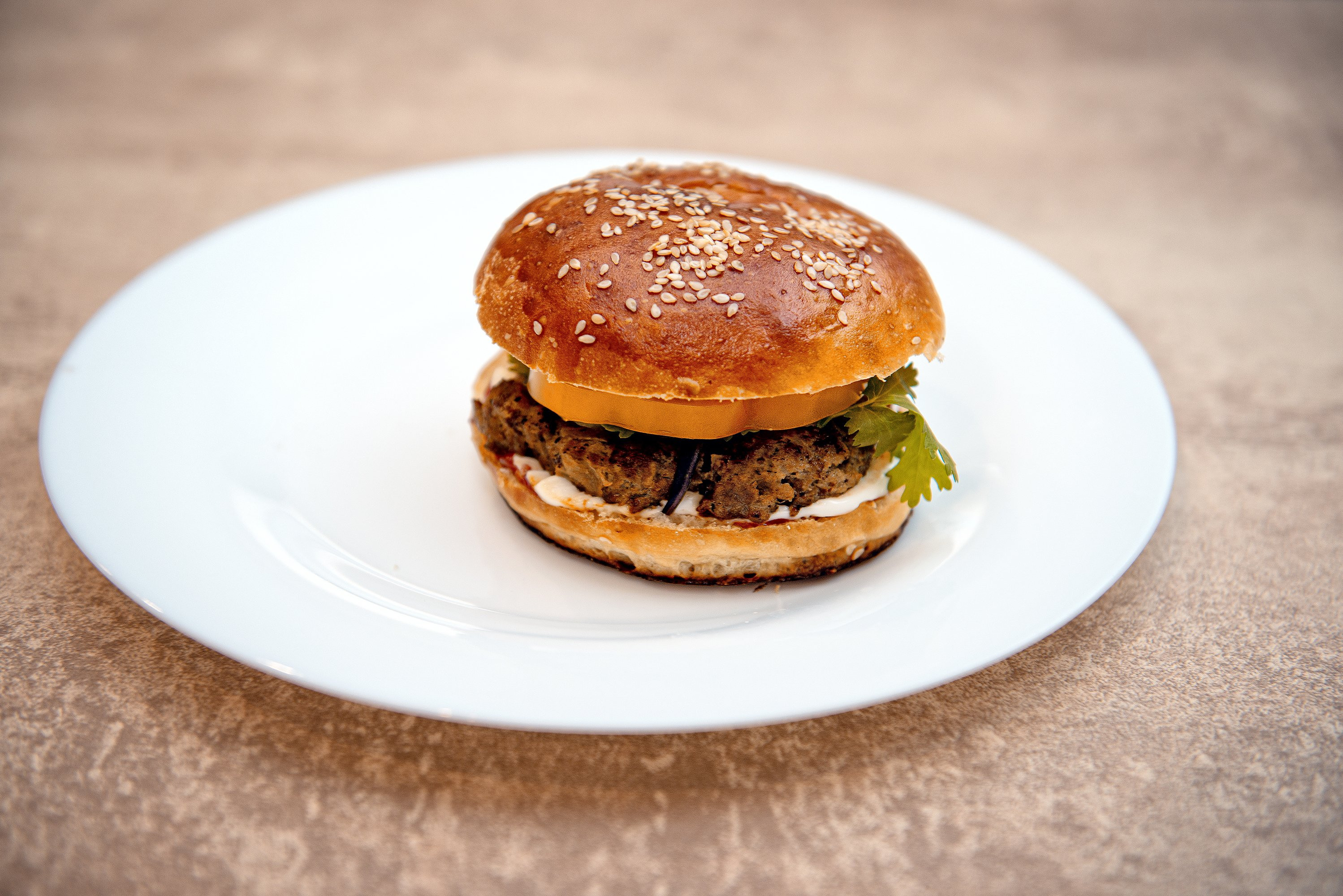 Homemade hamburger with fresh vegetables on white plate example image 1