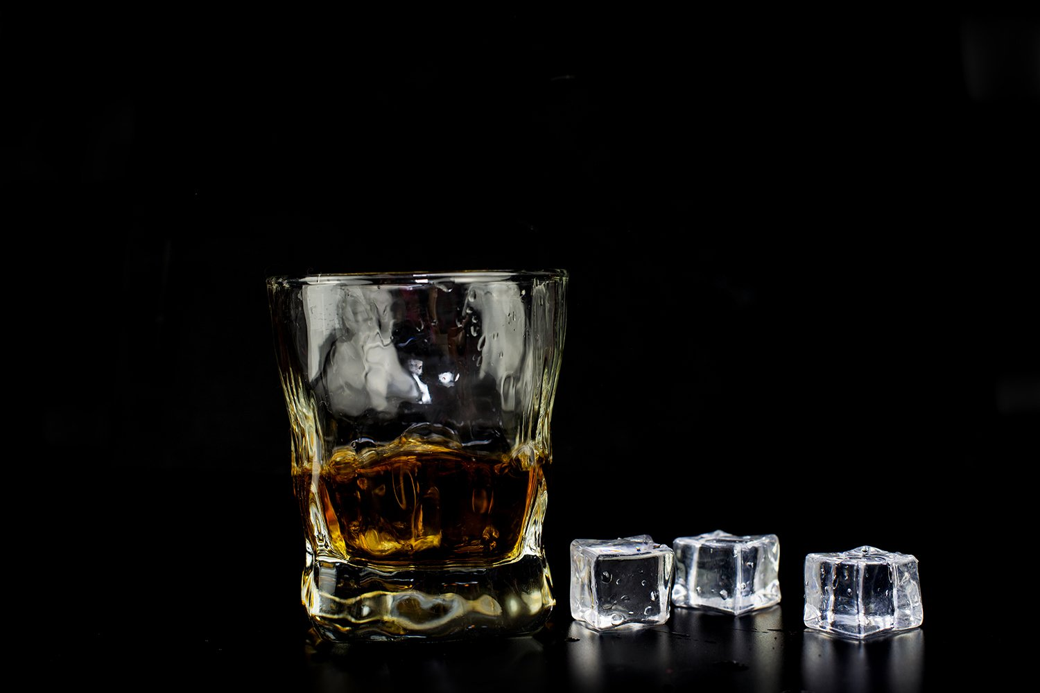 alcohol drink whiskey with ice cubes on a black background example image 1