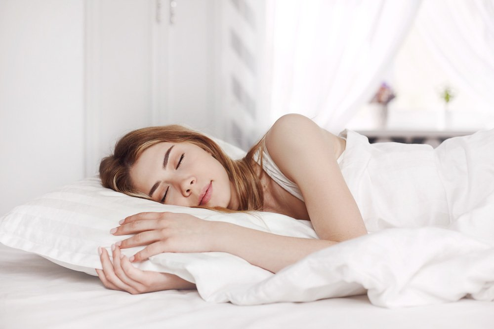 An attractive young girl in white pajamas sleeps on a bed example image 1