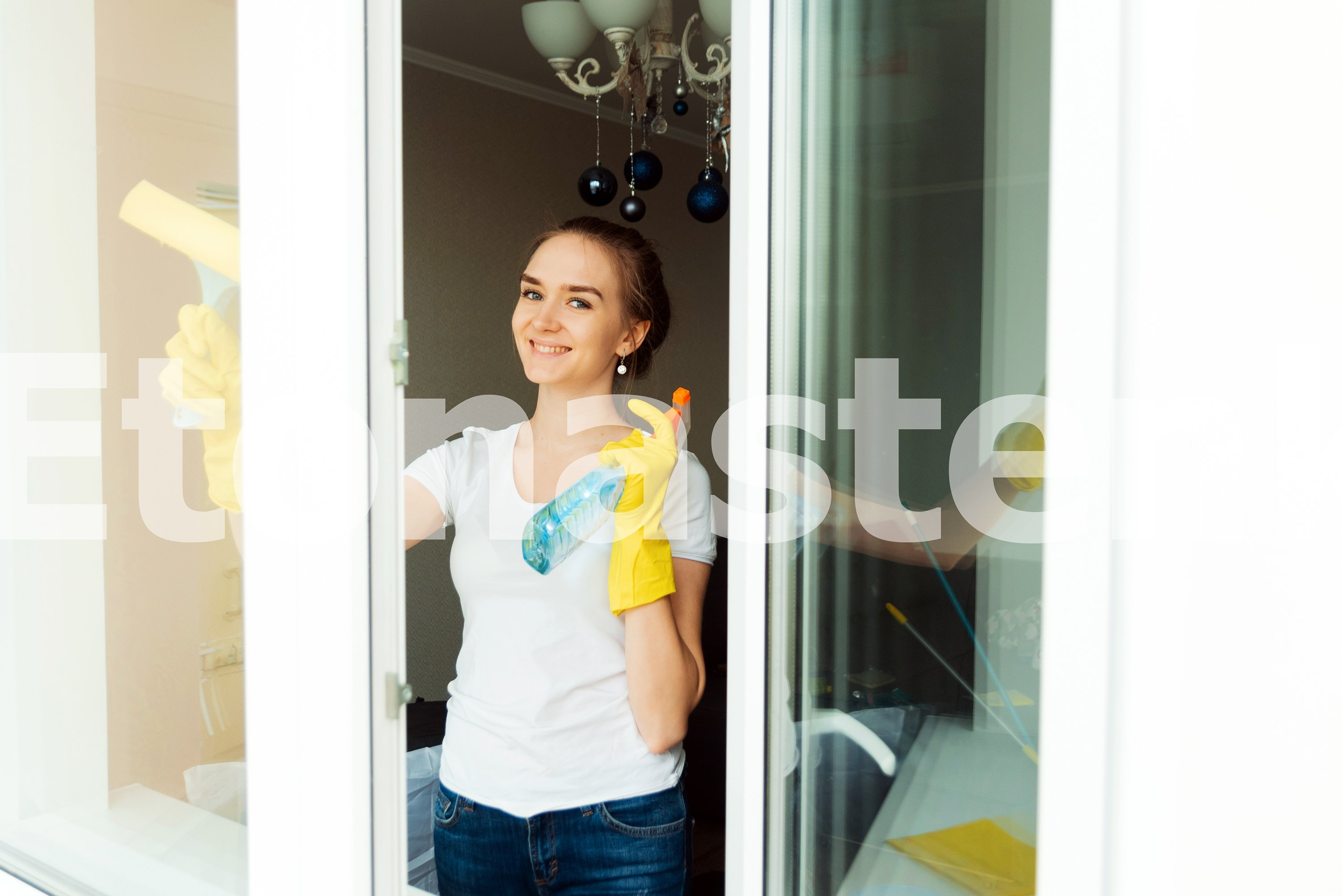 A cute adult female cleaning company worker wipes windows example image 1