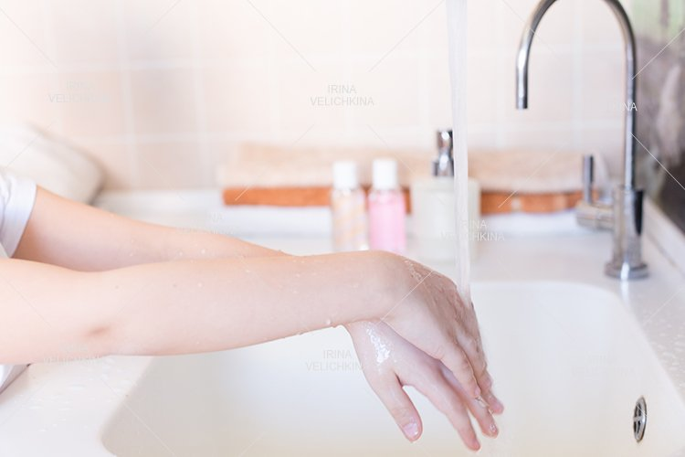 Girls wash their hands in the sink with soap in the foam example image 1