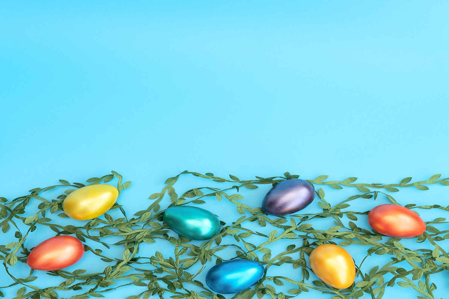 Decorated Easter eggs lie on green leaves example image 1