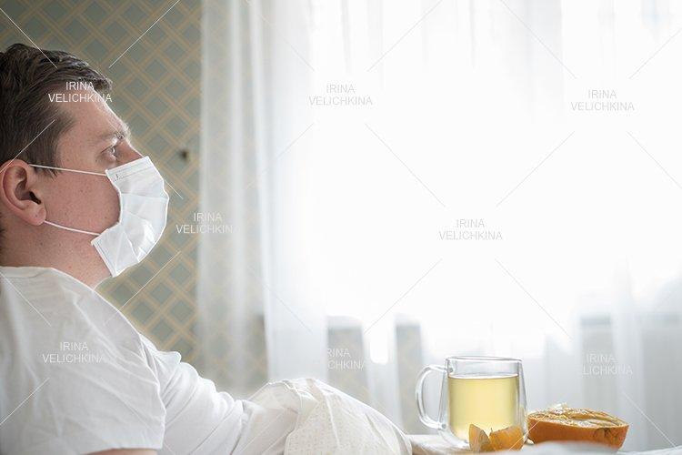 Sick man in bed. Face mask. Cup of tea, orange,lemon,ginger example image 1