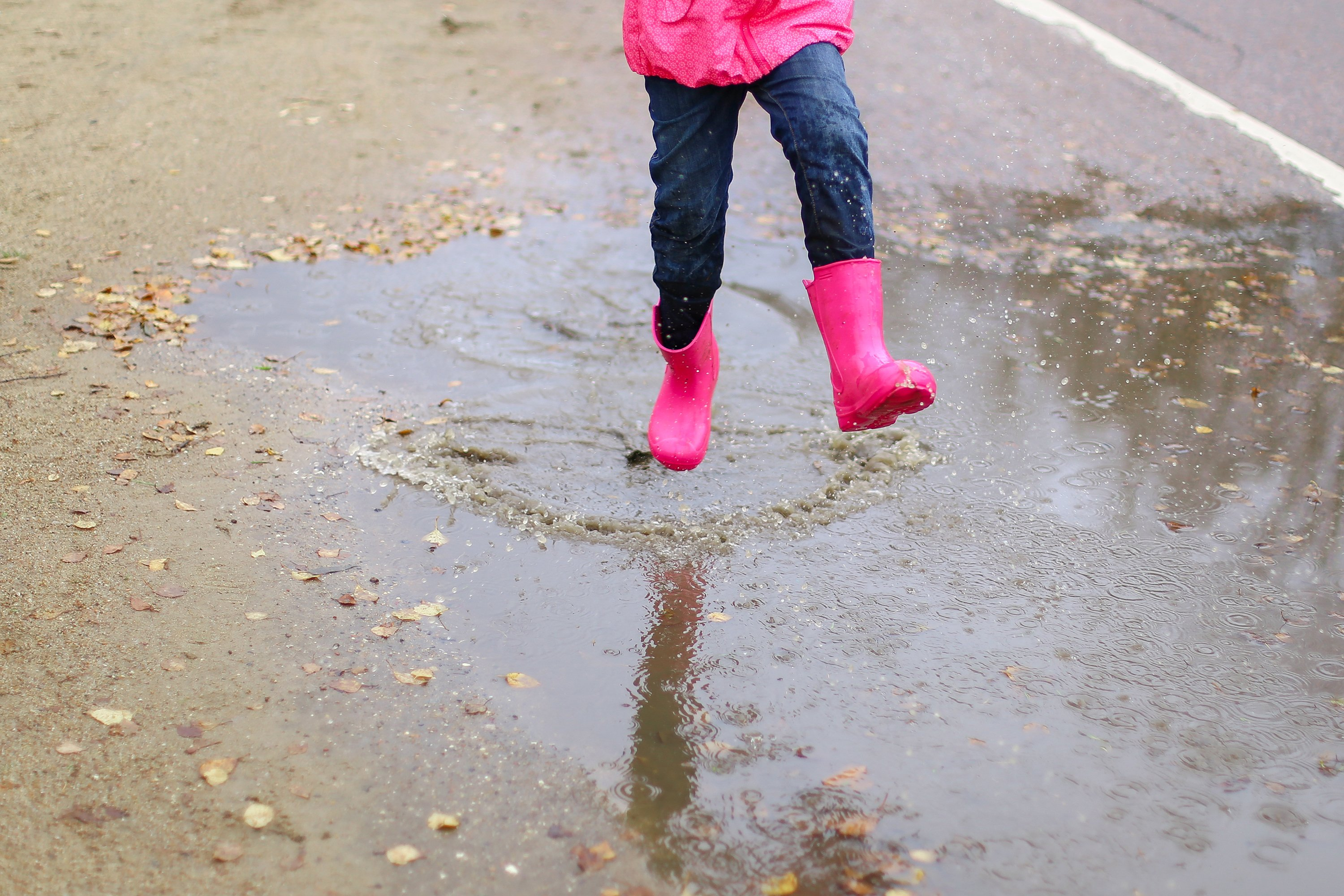 Girl in pink rubber boots jumps through puddle.Spring,autumn example image 1