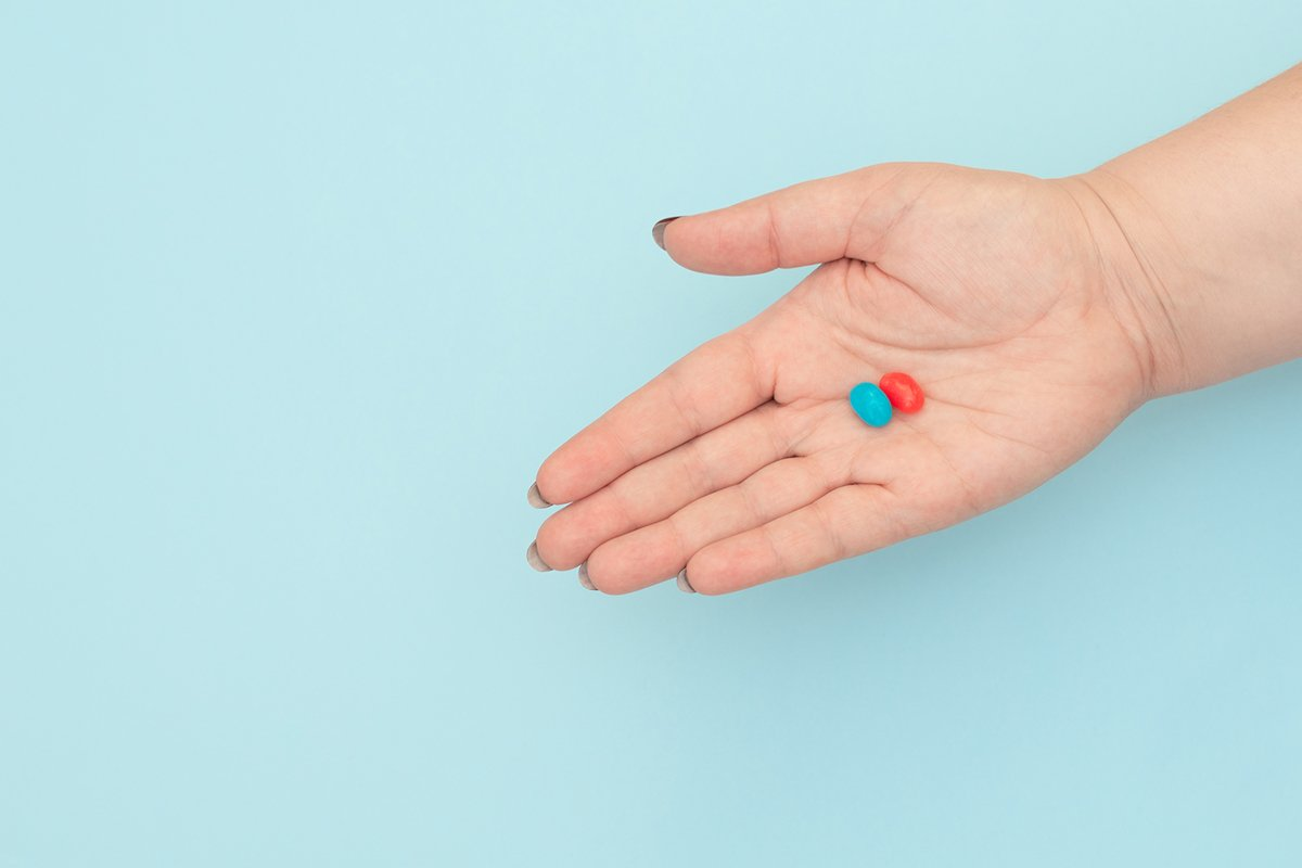 Red and blue pills on female hands on blue background. example image 1