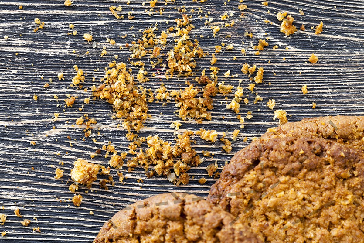 broken cookies with crumbs on the table. example image 1