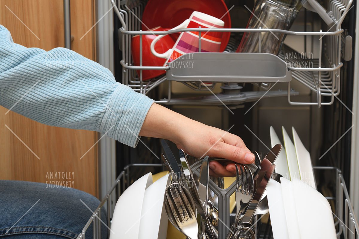 Female hand taking clean dishes out of dishwasher example image 1