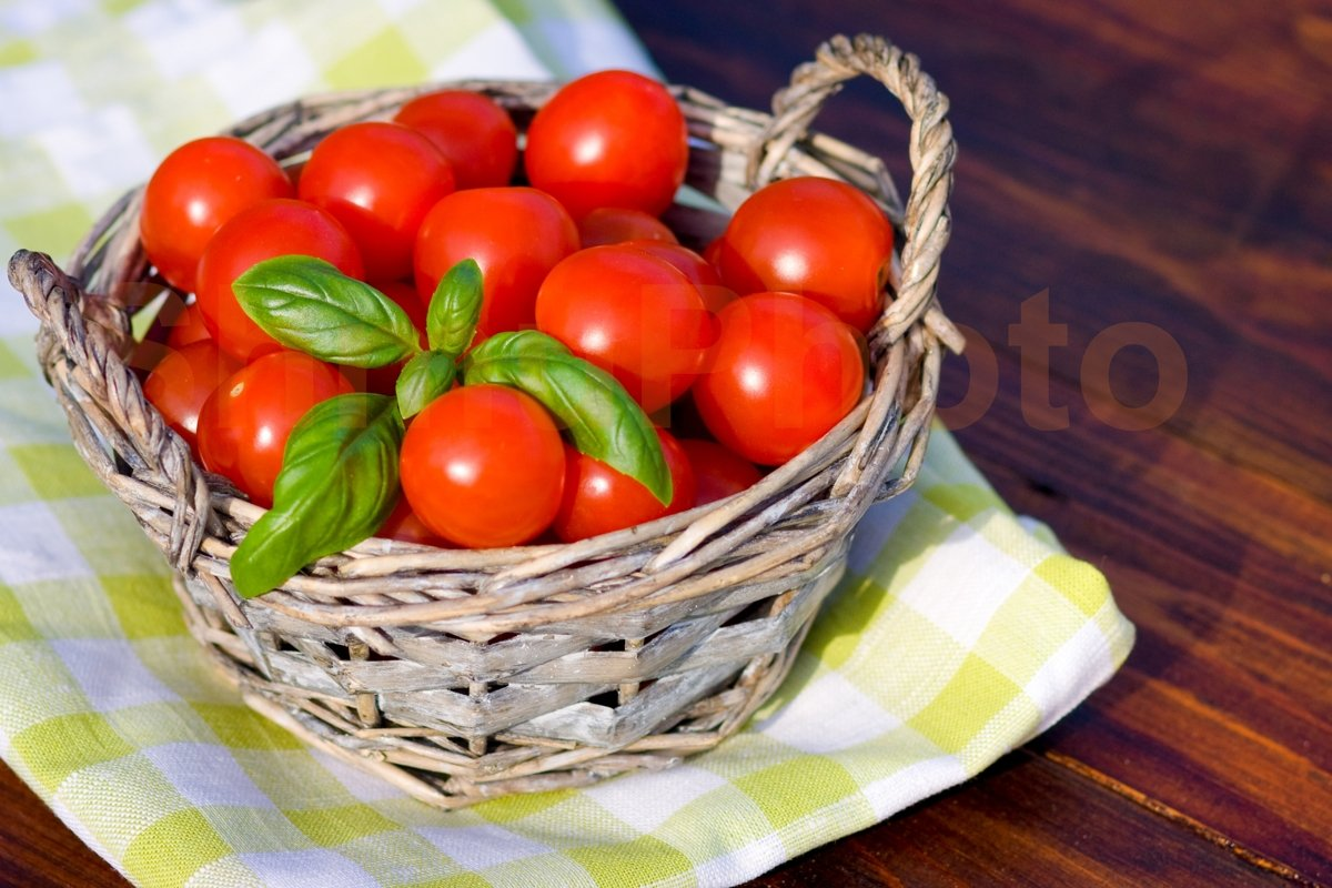 Tomatoes with basil in basket outdoors example image 1