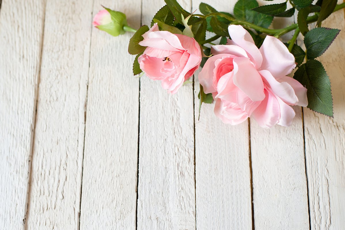 two pink roses on old wooden table example image 1