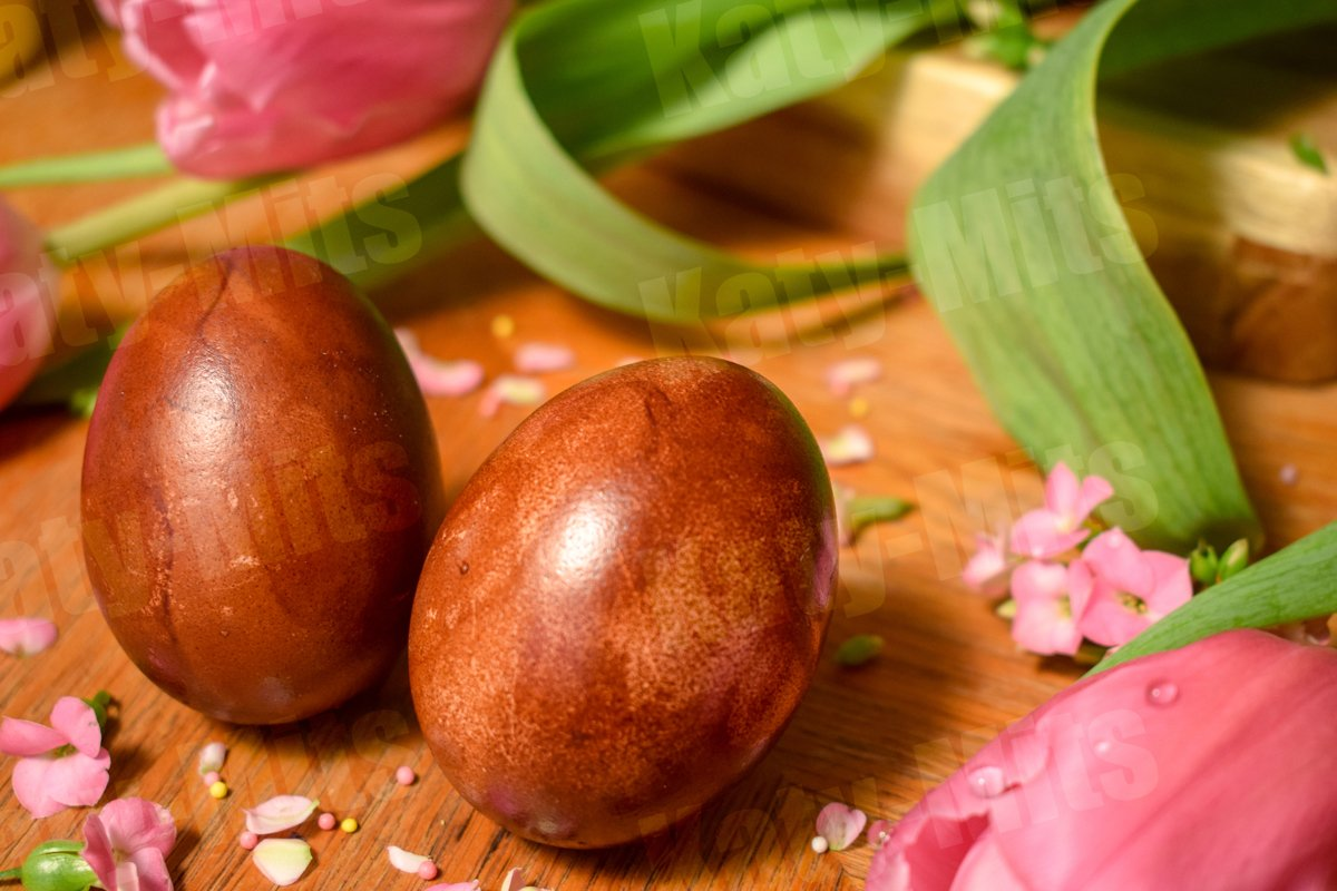 2 Easter eggs on a wooden table with pink flowers and petals example image 1