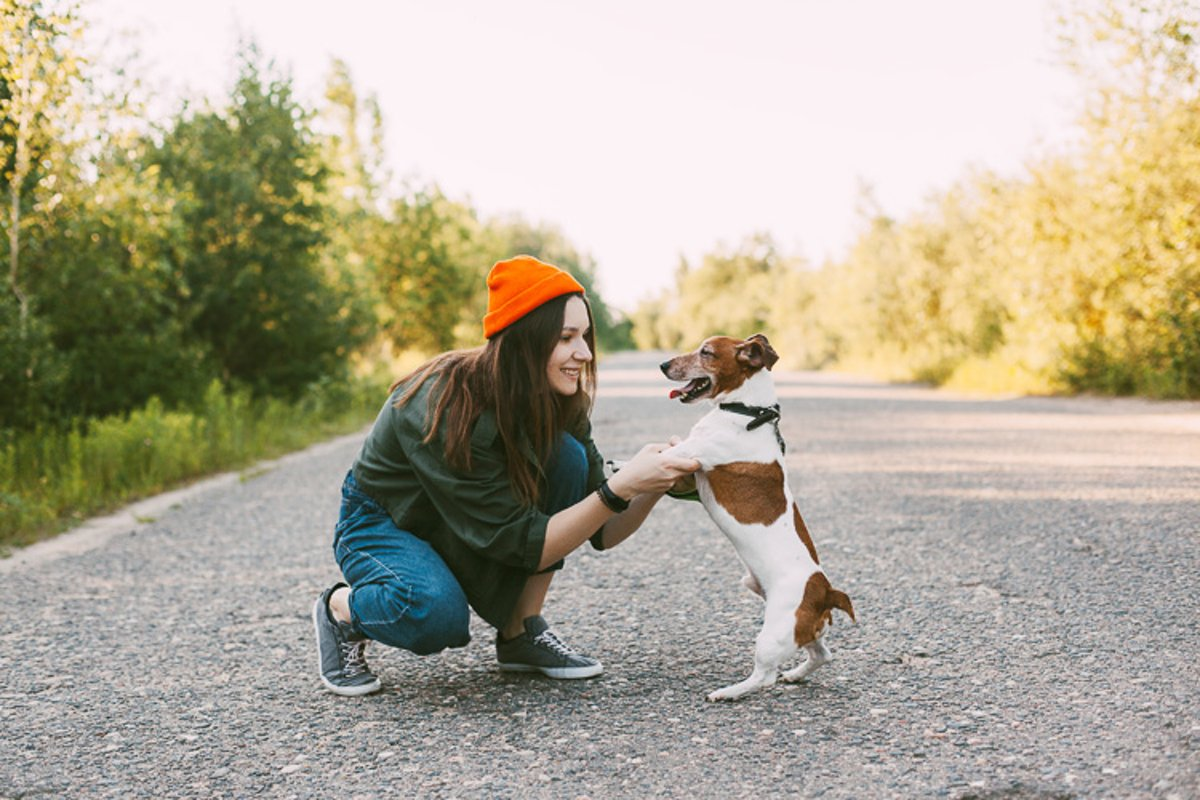 A girl in a green jacket and an orange hat walks with a dog example image 1