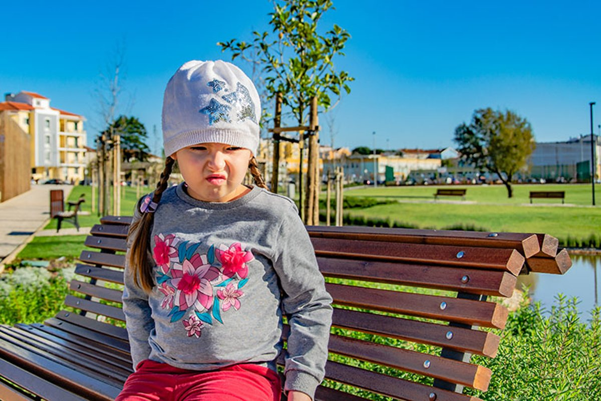 Sad little girl is sitting on a bench in the park. example image 1