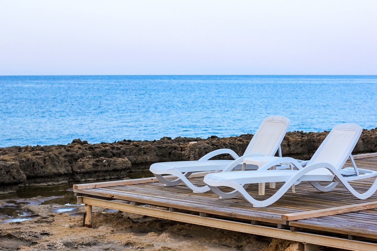 Tropical beach view with white empty chairs example image 1