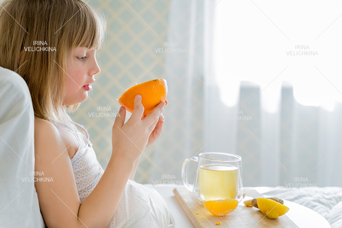 Sick girl in bed. Cup of flu drugs. Tea, orange,lemon,ginger example image 1