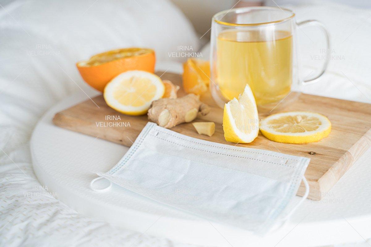 Cup of tea, orange,lemon,ginger. Face mask. Sick man in bed example image 1