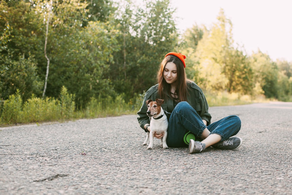 The dog is sitting in front of the girl on the road. example image 1