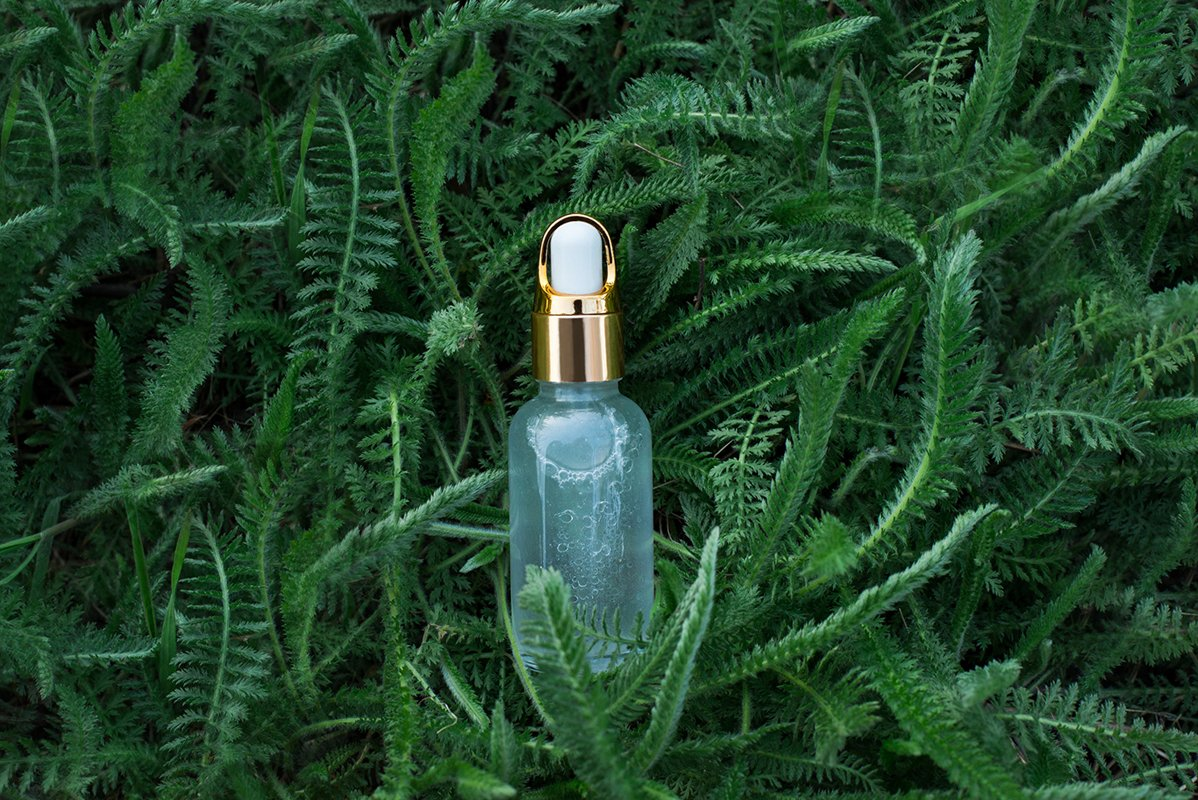 Natural herbal cosmetic oil in background with green grass. example image 1