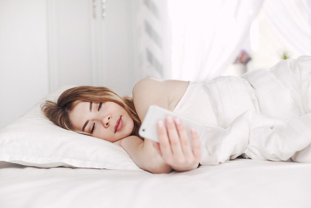 Beautiful young girl looks at the phone while lying example image 1