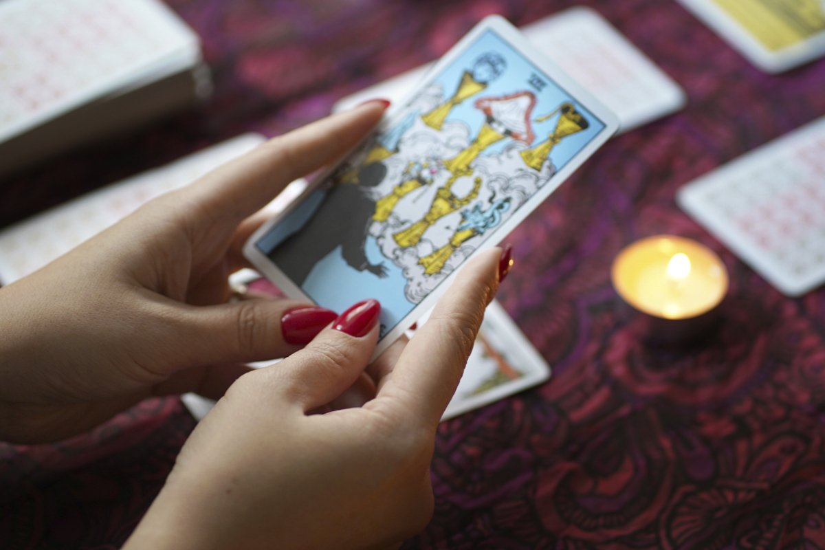 Tarot cards on table near burning candles example image 1