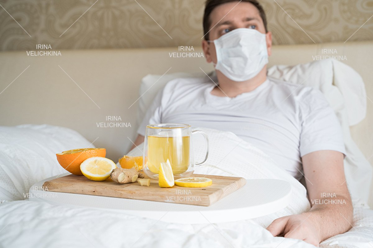 Sick man in bed. Face mask. Cup of tea, orange,lemon,ginger example image 1