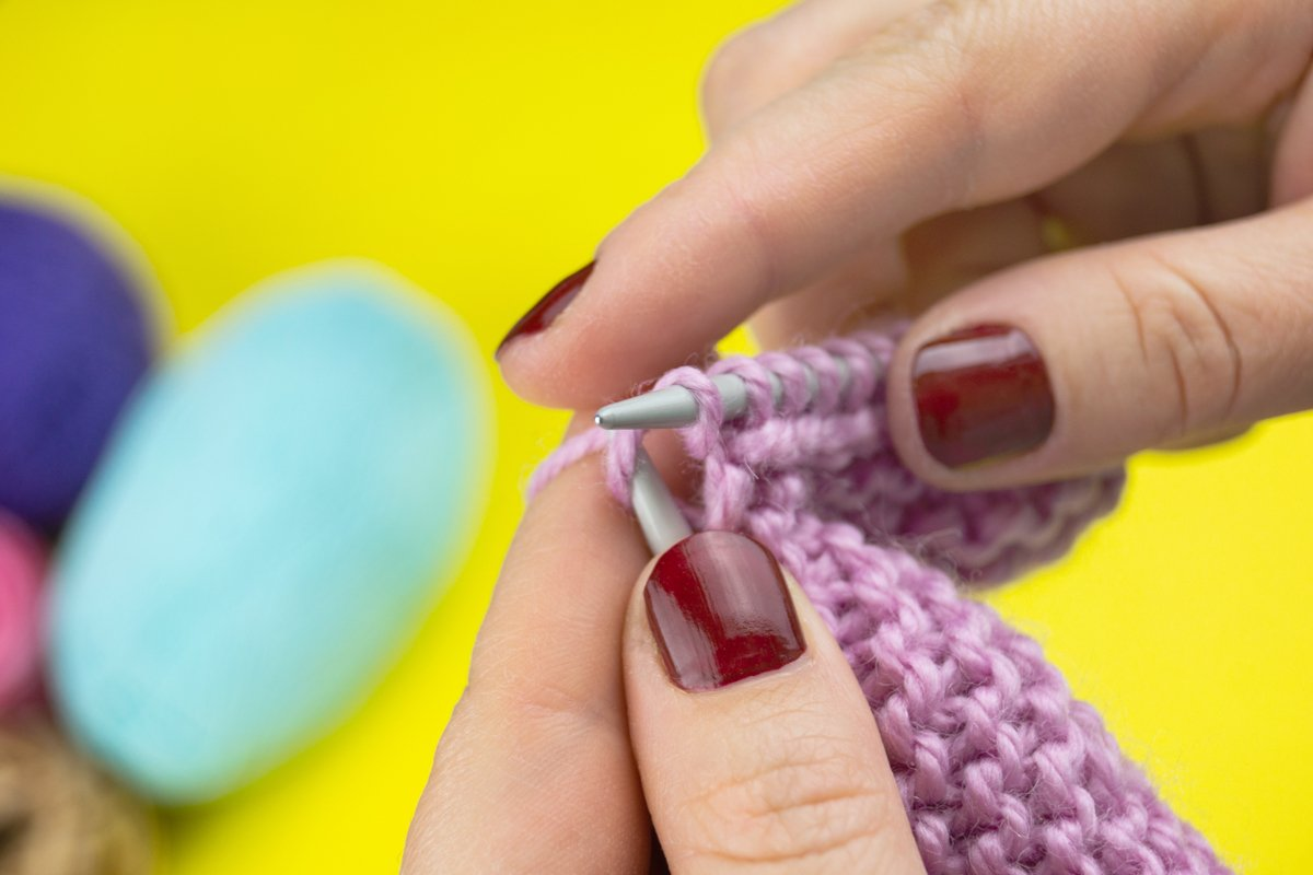 the girl knits a children's scarf on a yellow background example image 1