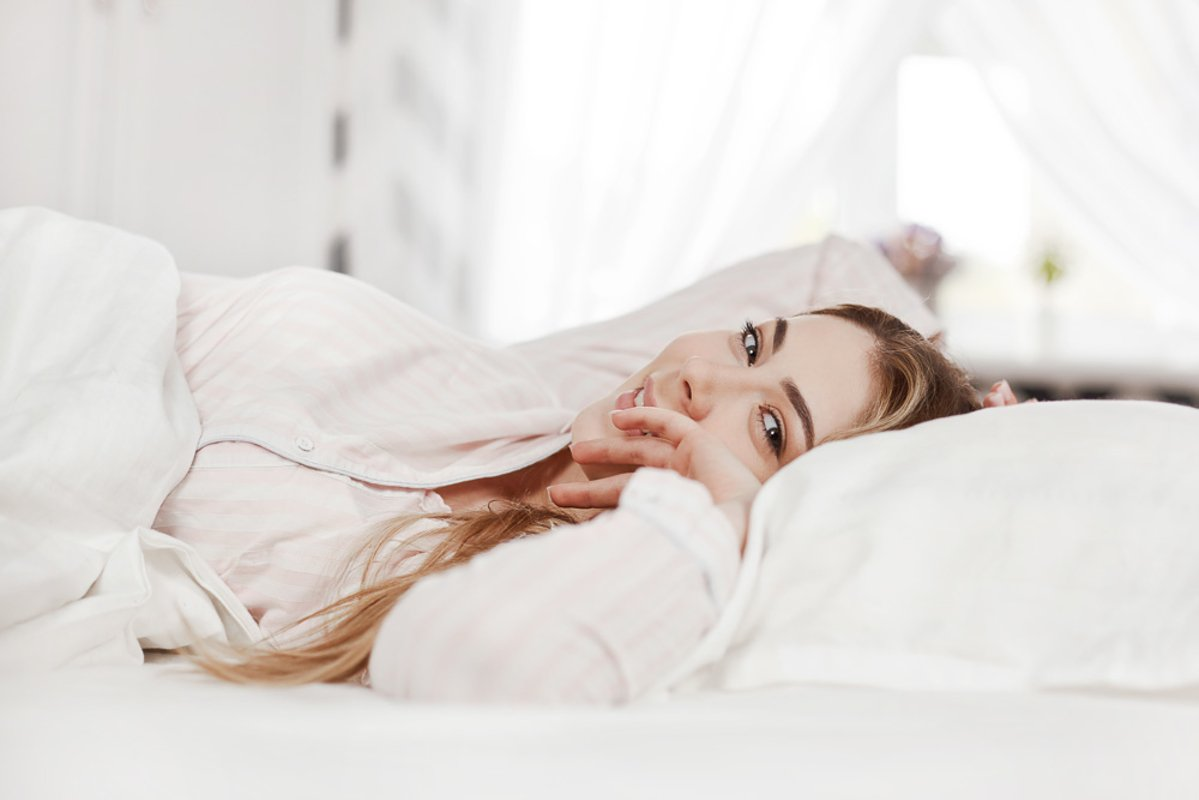 A young smiling girl is lying in bed in the bedroom example image 1