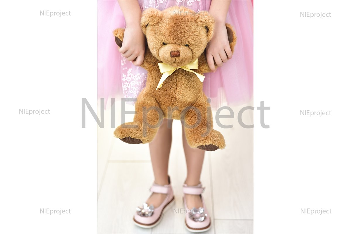 Child in pink dress with teddy bear. Close up example image 1