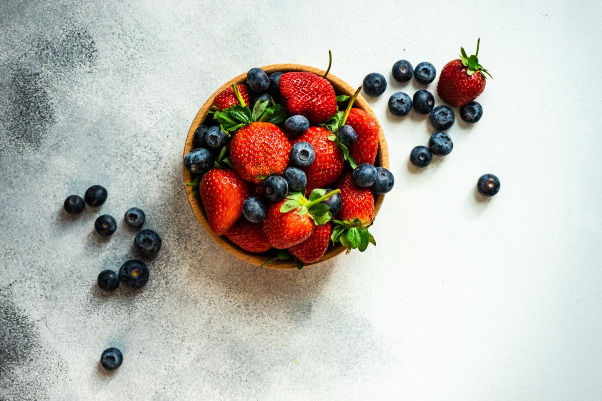 Organic summer berries in wooden bowl full of strawberries example image 1