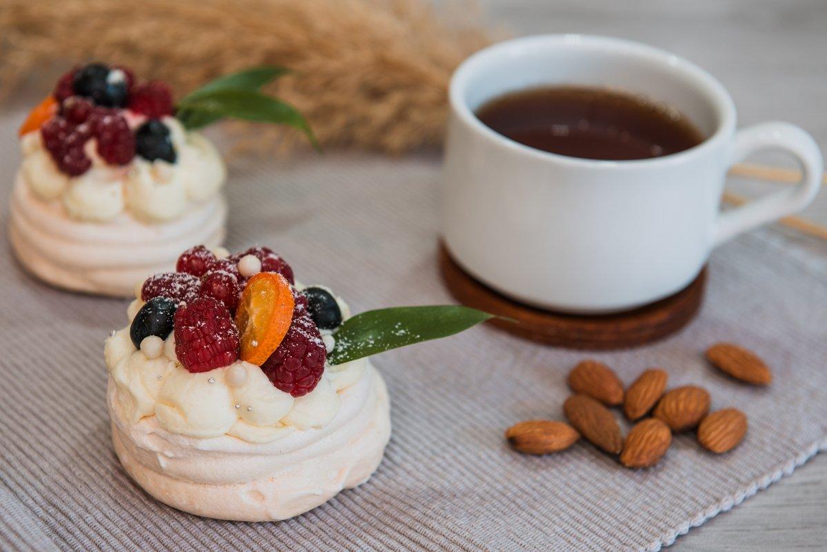 Pavlova meringue desert cake with cream and small fruits example image 1