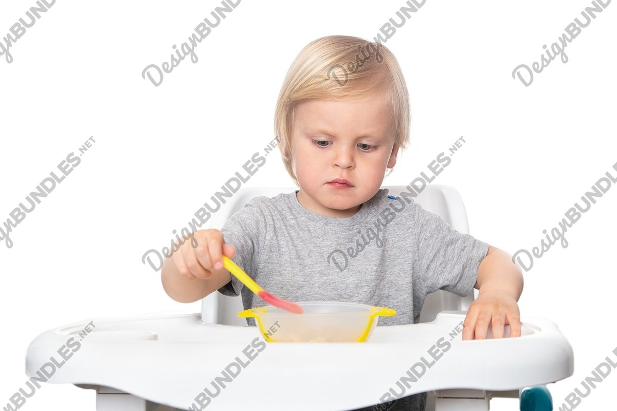 Cute boy with a spoon in his hand on the white background example image 1