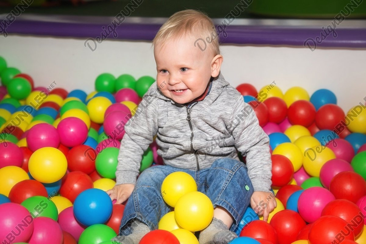 Smiley baby boy plays with colorful balls in playground example image 1