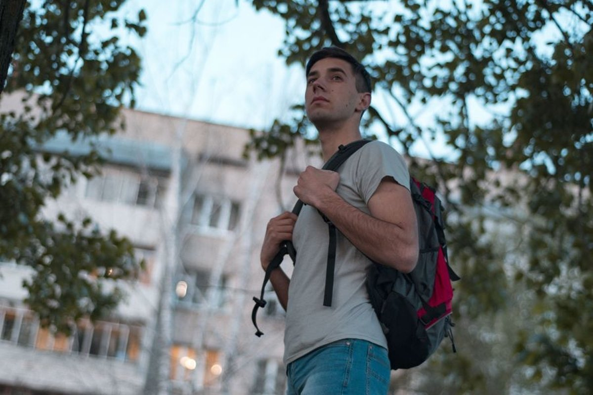 Young caucasian man walks in a park with backpack example image 1