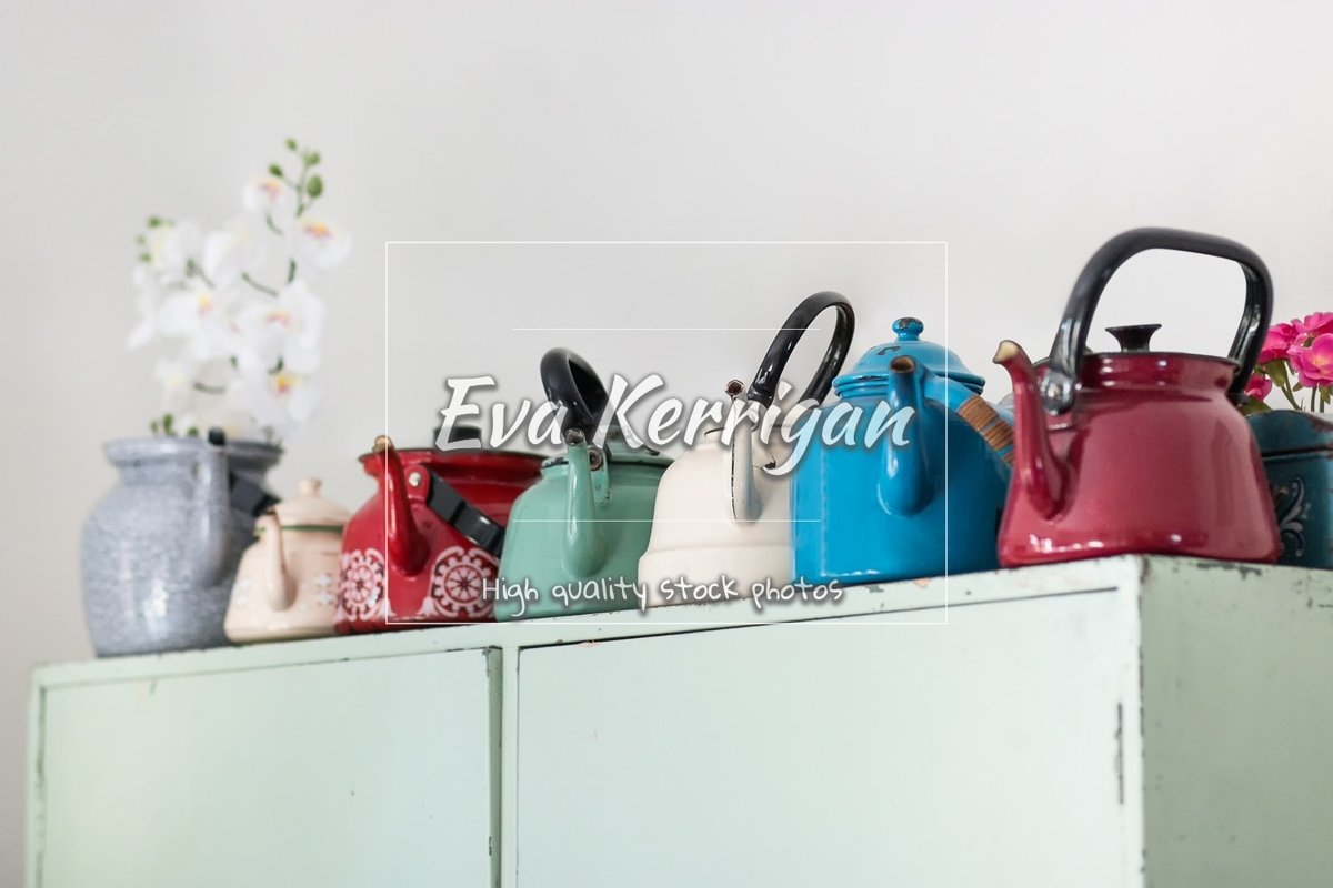 Old metal multi-colored teapots stand on a wooden cabinet. example image 1
