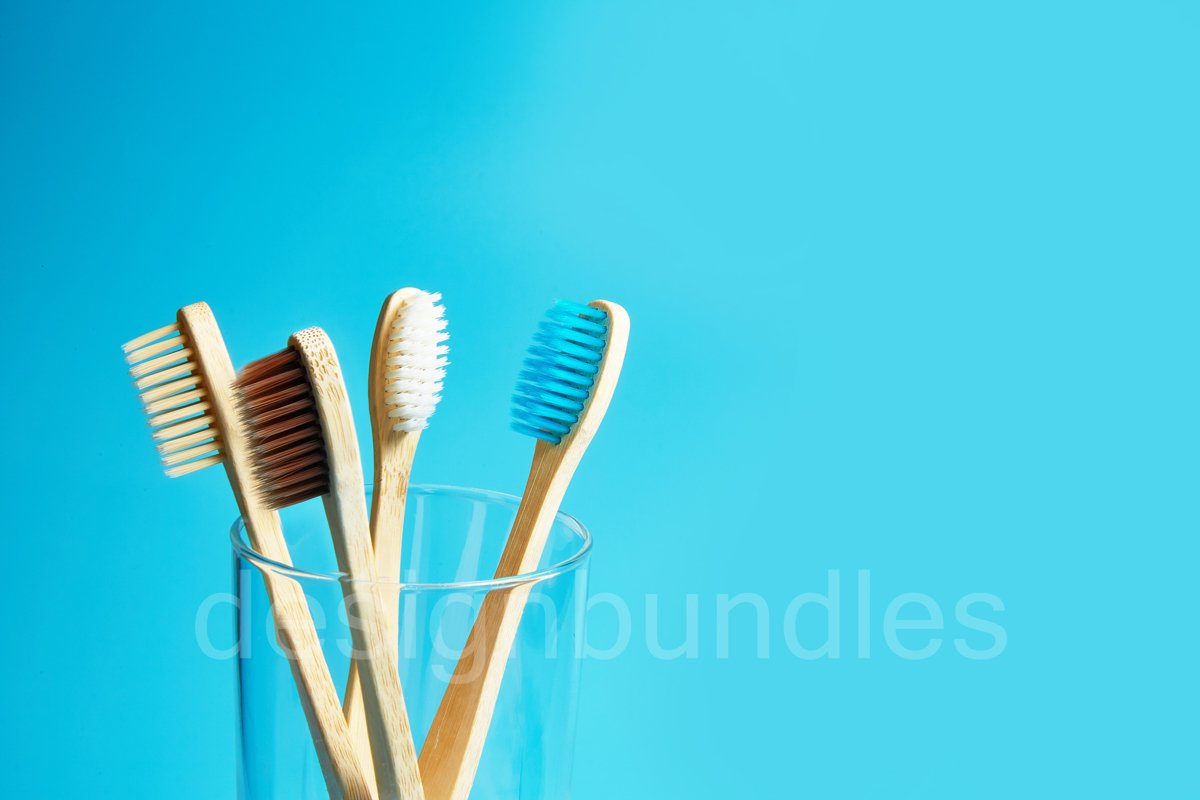 Wooden toothbrushes with a glass cup on a blue background example image 1