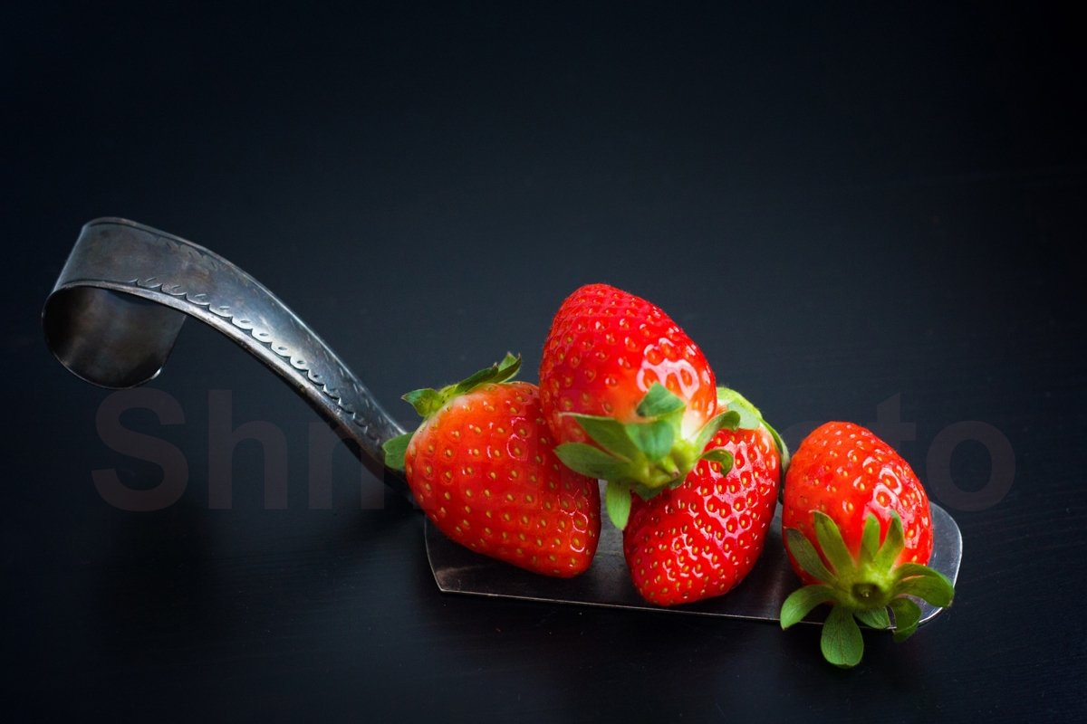 Fresh strawberries at silver spatula on black background example image 1