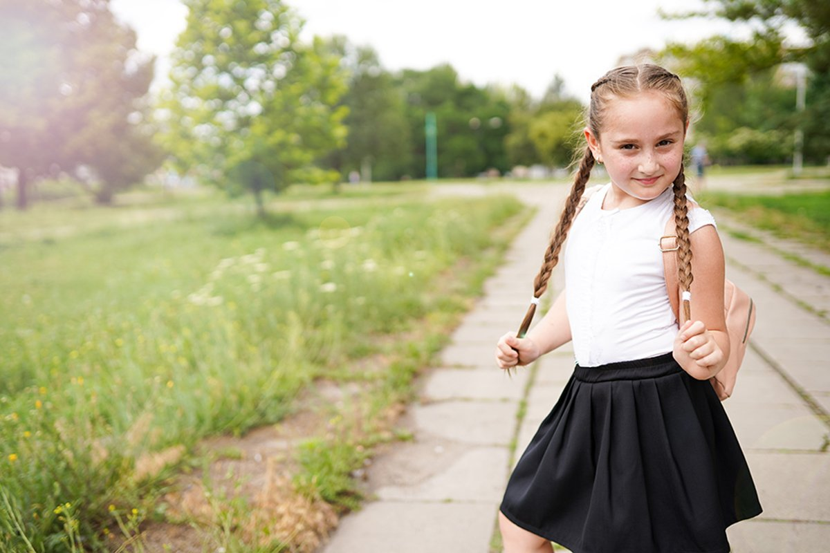 Little school girl in uniform holding her pigtails example image 1
