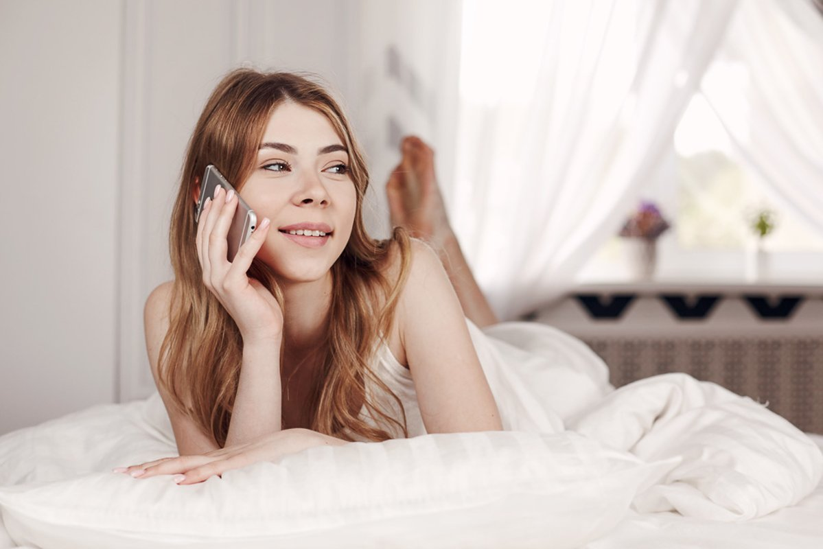 Cute smiling girl looks at the phone, lying on the bed. example image 1