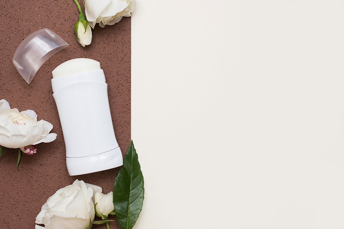 Flat lay composition with deodorant and flowers example image 1