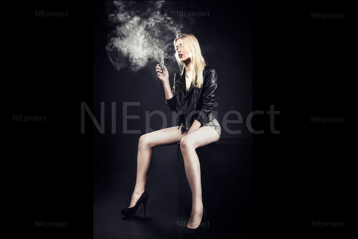 relaxed cute girl model smokes vape in studio example image 1