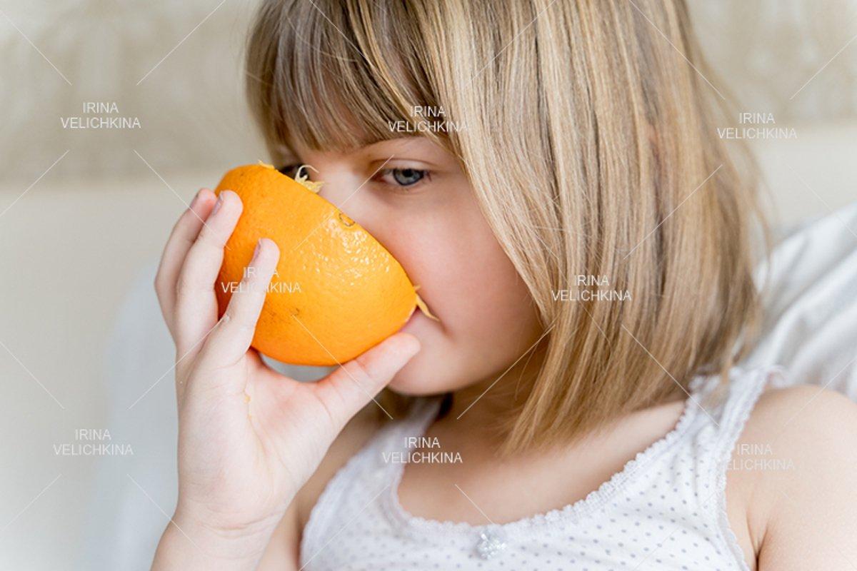 Sick girl in bed. Eating big orange in hands example image 1