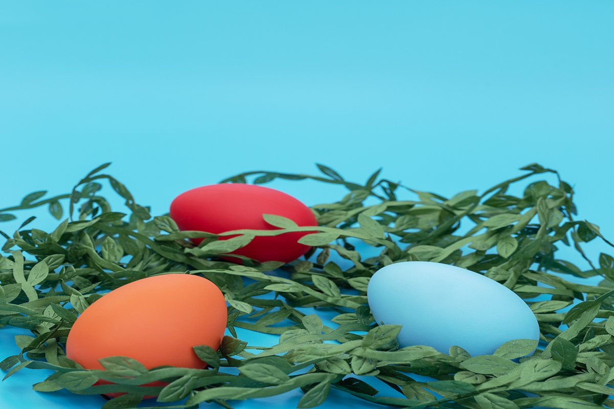 Easter eggs lie on the green leaves on blue background example image 1