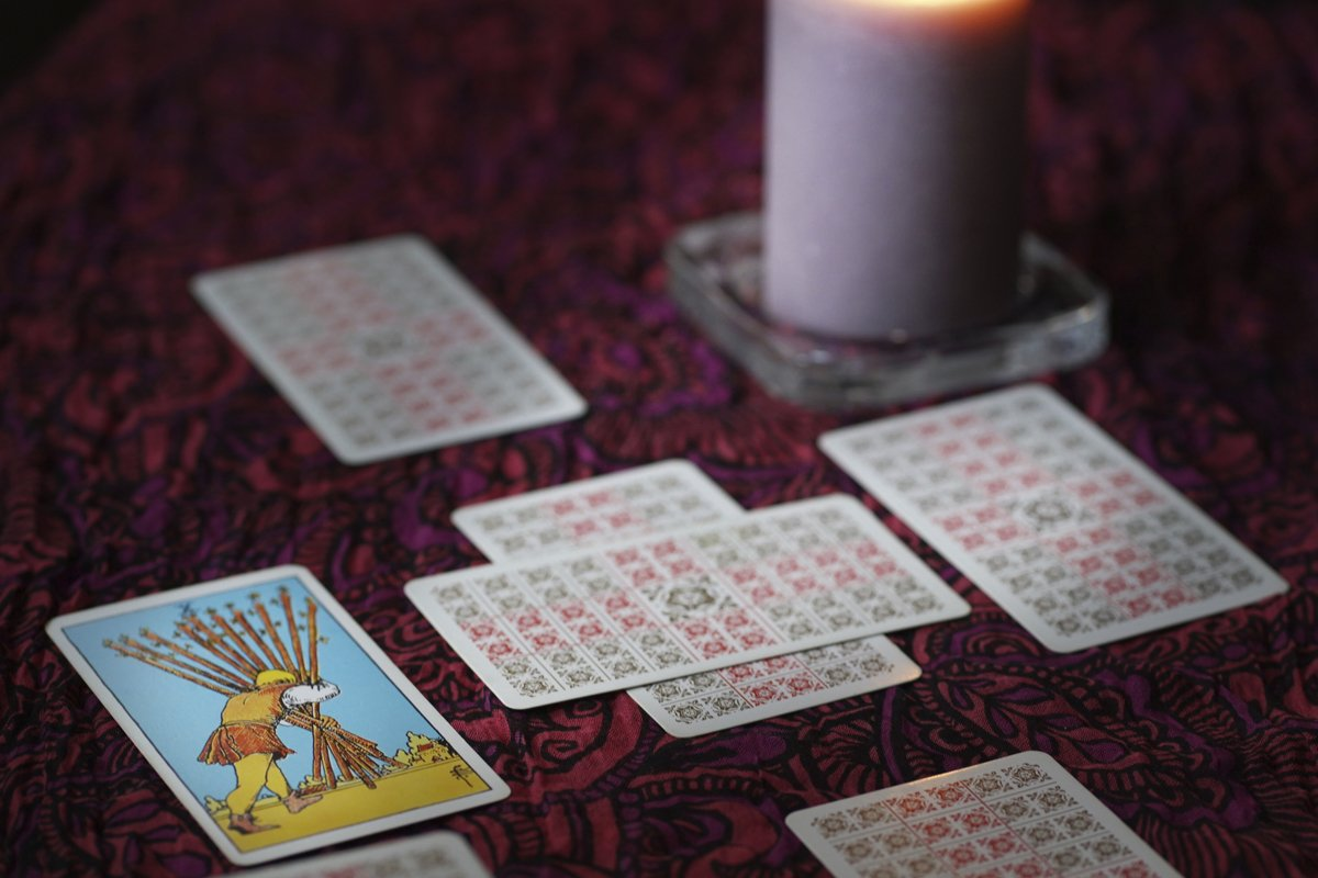 Tarot cards on table near burning candles, esoteric concept example image 1