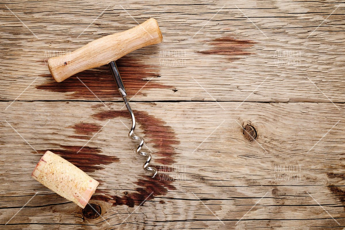 Corkscrew, cork and wine stains on wooden background example image 1