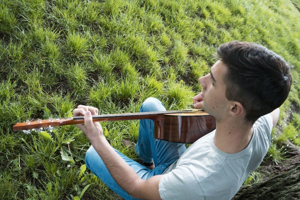 Young caucasian man with guitar in the park example image 1