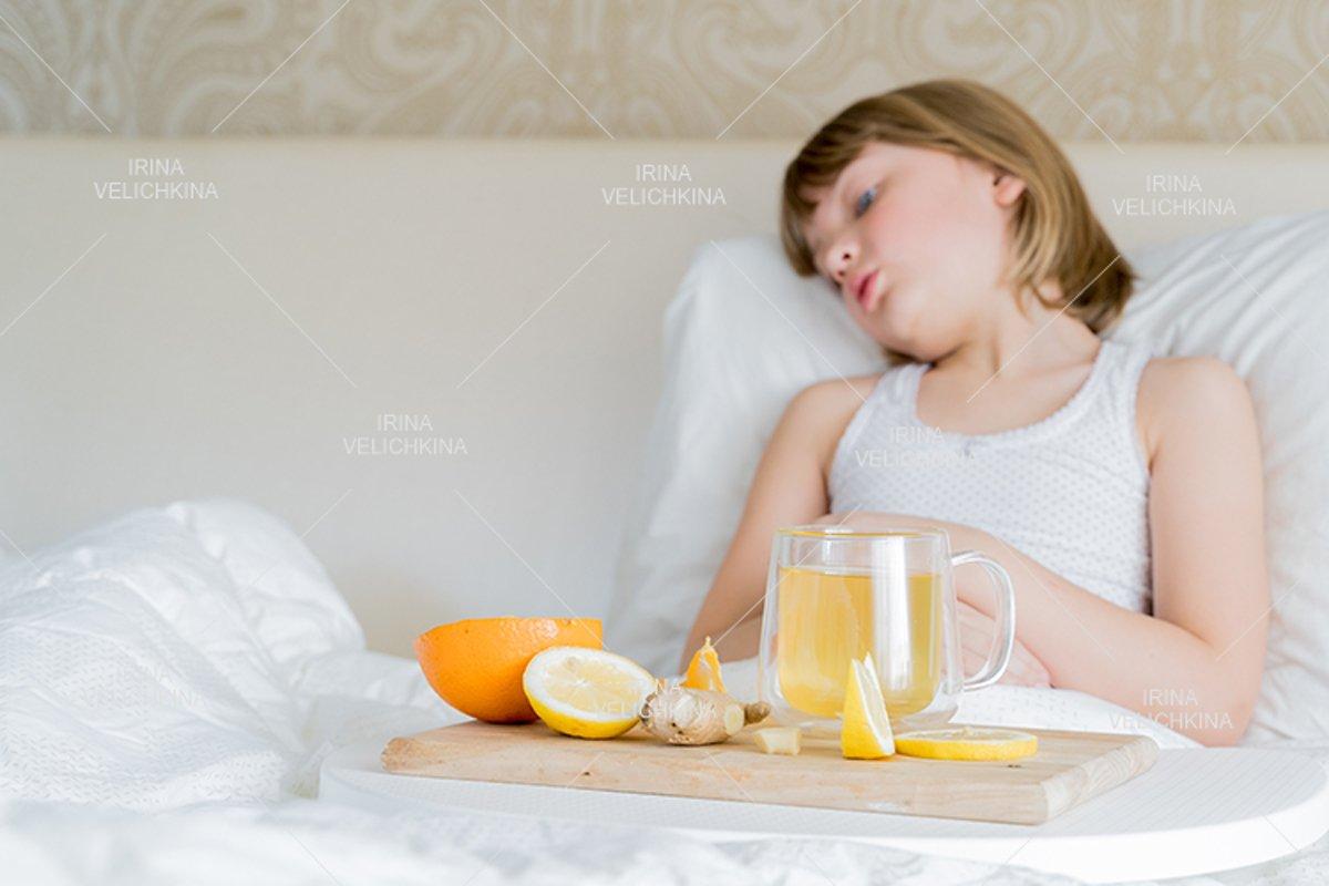 Sick girl in bed. Cup of flu drugs. Tea, orange,lemon,ginger example image 1