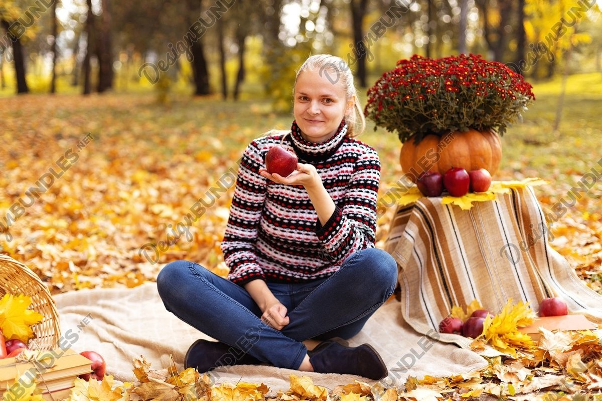 Photo of a Woman with apple on a picnic in the park example image 1