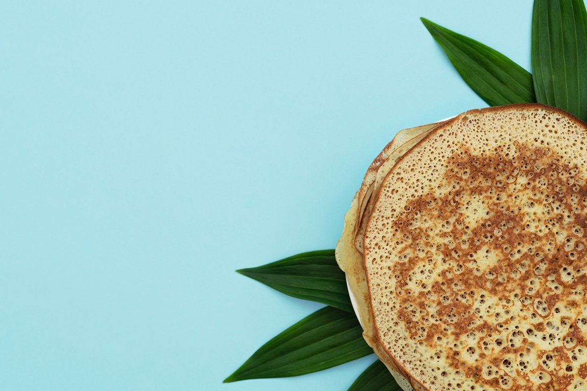 Homemade pancakes on blue background with green leaves example image 1