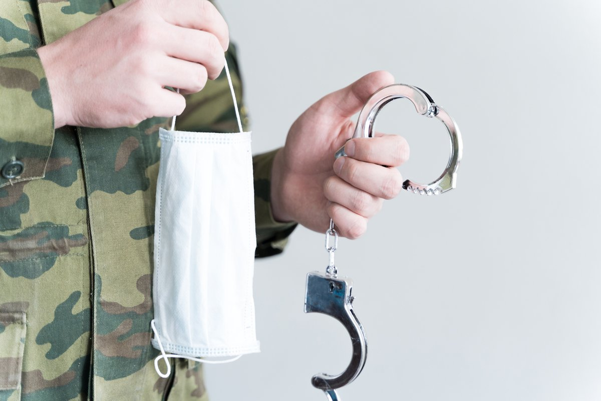 Officer with handcuffs. Face mask. Isolation violation fine example image 1