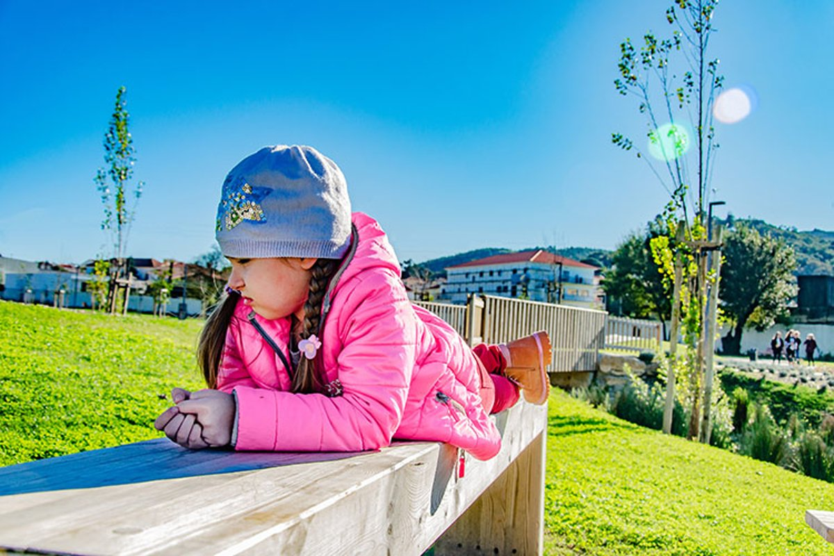 Sad little girl is on a bench in the park. example image 1